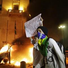 Carro da Record incendiado ao fundo, São Paulo (Foto: AP Photo/Nelson Antoine)