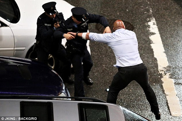 Breaking free: He pushed the arresting officer into the gun-toting one