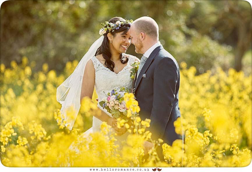 Bride and groom in rapeseed field in Suffolk - www.helloromance.co.uk