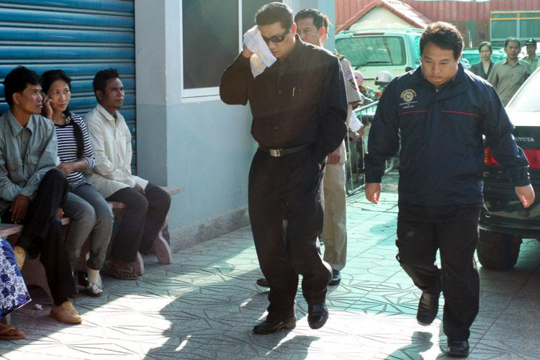 Ray Chhat Dam (left), chairman of ARP-OITC group, enters Phnom Penh Municipal Court in 2010.