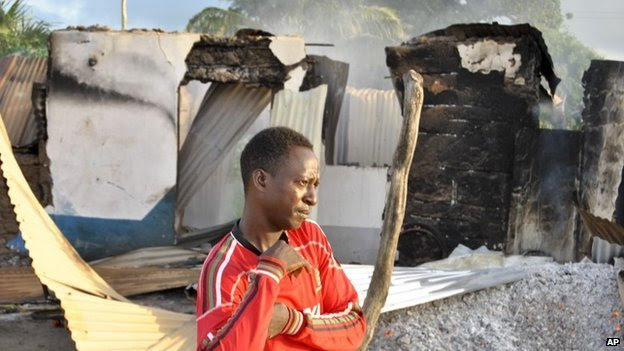 A man stands in front of the still-smouldering shell of a building set on fire by militants in the town of Mpeketoni on the coast of Kenya on 16 June 2014
