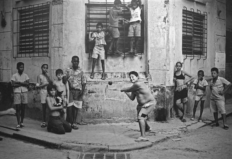 """Kids playing stickball in Havana, 1999. By Cliff. Wikipedia/Flickr (CC BY 2.0) """"There's a famous picture taken in the '50s of Willie Mays playing stick ball in Harlem. I played a lot of stick ball growing up and always loved it. I wanted to replicate the Mays photo in Cuba because baseball is the national sport there. It's everywhere. Cuban children play ball in the streets like kids in U.S. cities used to do. It was my last Saturday on this trip and I was slowly weaving through the streets of old Havana, looking for kids playing ball, when I came upon this corner, La Esquina. If you study the picture, you see that every eye, not just the kids' but even the dog's, is on that taped ball. It's the decisive moment, and there's no way to anticipate when you're going to get it. I had a vision of a picture that I'd tried and tried and tried to find but hadn't yet, and I came within a day of not finding it. To me it was all about getting the photograph I'd been searching for and I did it in 20 frames."""""""