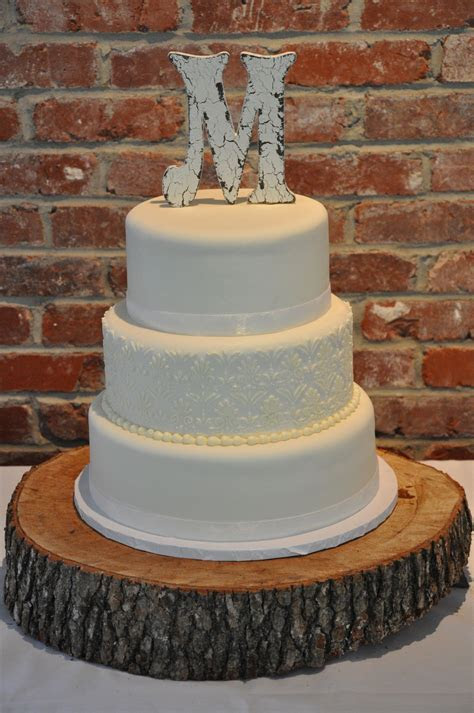"""Elegant three tier wedding cake with """"M"""" initial topper"""