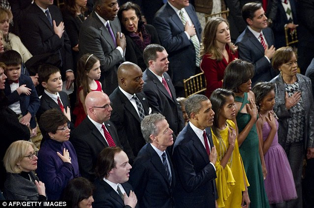 Pride: President Obama and his family stand to attention during the National Anthem at the carol concert which will air on Friday on TNT