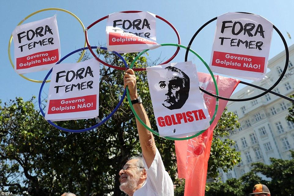"""Um manifestante segurava anéis olímpicos com um slogan que se traduz como """"Temer para fora! '  - Referindo-se ao presidente interino do Brasil Michel Temer, em São Paulo, Brasil"""