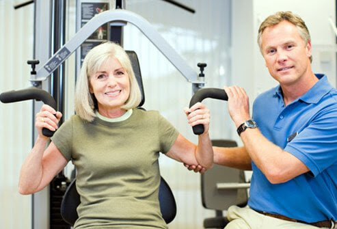 Woman exercising with trainer on weight machine.