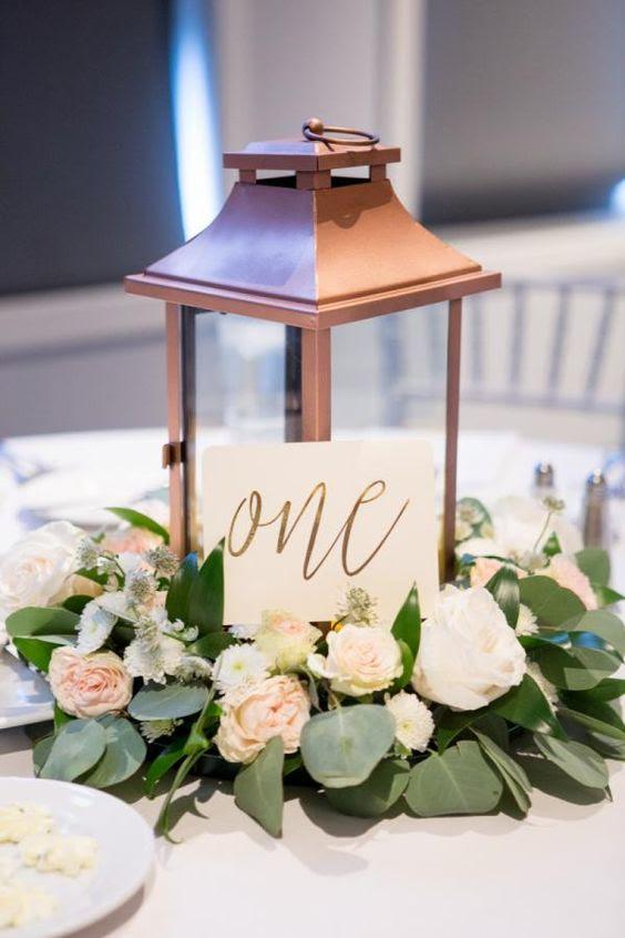 eine kupferne Laterne mit üppigen Blüten und einem Tisch Nummer für einen coolen Herzstück