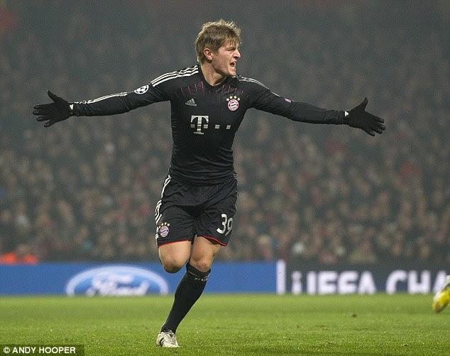 Glove affair: Germany midfielder Kroos celebrates his fine early strike at the Emirates Stadium