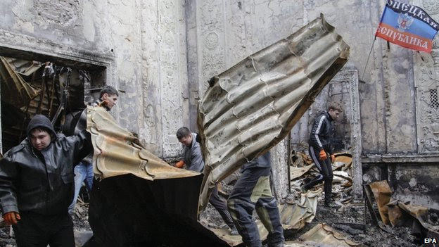 Volunteers sift through debris at the Cultural House in Donetsk, following shelling on Wednesday 24 December 2014