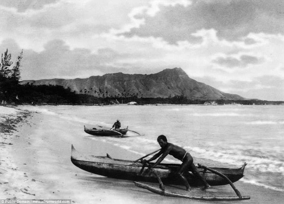 Two men push their outrigger canoes to shore in Honolulu, Hawaii, as the waves lap the sandy beach in a picture taken around 1922