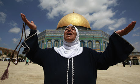A Palestinian woman prays in front of the Dome of the Rock in Jerusalem's Old City