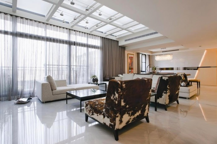 With the ultimate use of natural light in mind, designers Artenid created this contemporary home with a wall of windows spanning the living room and a grid of skylights spanning the width of the room. White marble was used throughout the space to bounce light deeper into the home's interior.