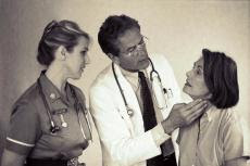 Photograph of a male doctor and female nurse examing a female patient