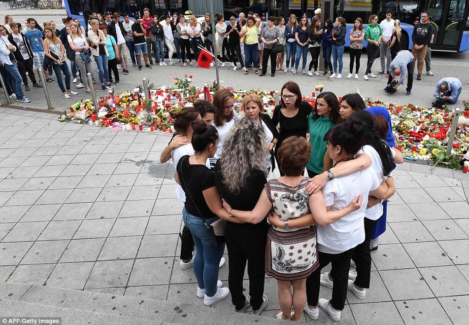 As pessoas choram em frente de velas e flores perto do shopping Olympia compras em Munique, sul da Alemanha, onde um estudante alemão-iraniano de 18 anos de idade, correu amok em um tiroteio em 22 de Julho