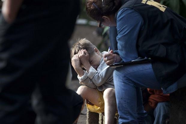 Sobrevivente Carlos Daniel Gonzalez, 6, conta para polícia nesta quinta-feira (10) como se escondeu durante ataque que matou sete membros da sua família na quarta-feira (Foto: EFE/Saul Martínez)