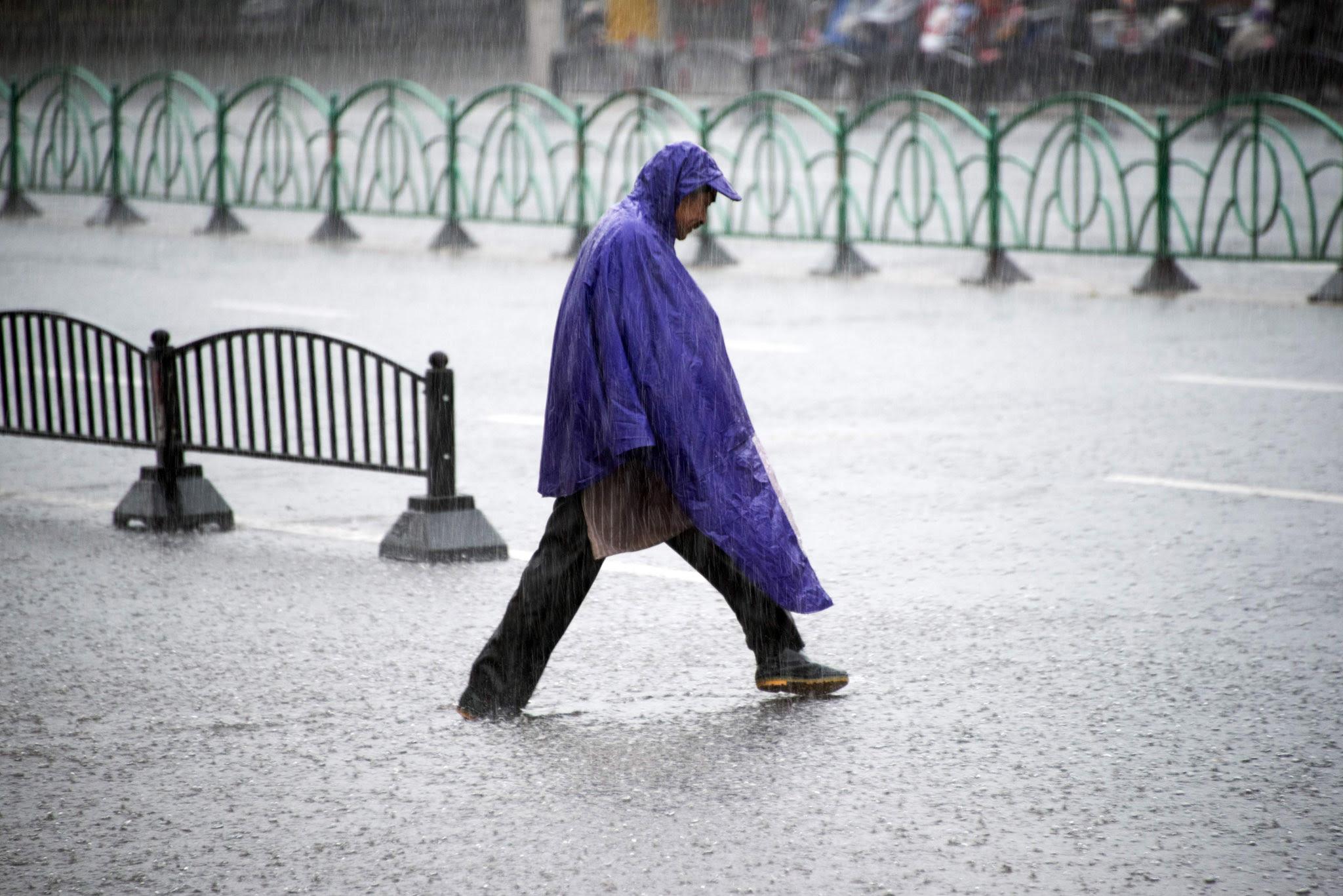 A man crosses a flooded street during rainfall in Shanghai