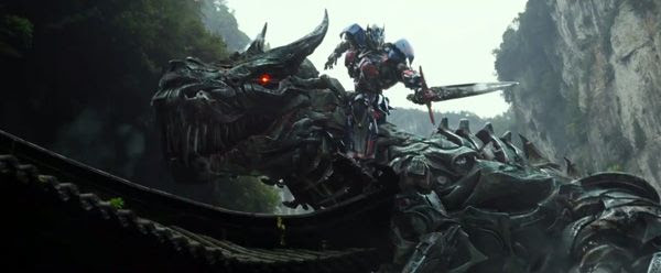 A battle-ready Optimus Prime hitches a ride atop Grimlock in TRANSFORMERS: AGE OF EXTINCTION.