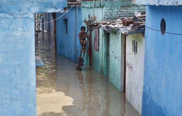 A boy sits on a ladder next to his flooded house with the rising water level of river Yamuna after heavy monsoon rains in New Delhi, June 19, 2013.  REUTERS-Anindito Mukherjee
