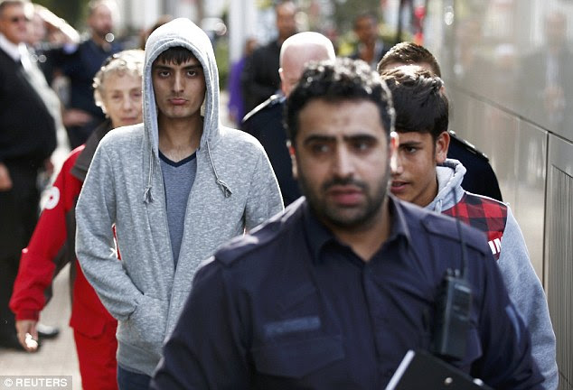 UK Border Force staff escort the first group of unaccompanied minors, pictured in gret hooded tops, to the Home Office