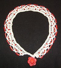 A bead crochet necklace made from mercerized cotton and coral.  This piece is worked in alternating beaded and non-beaded rows in order to align a comfortable lace surface against the wearer's collar while it displays beads to the viewer.