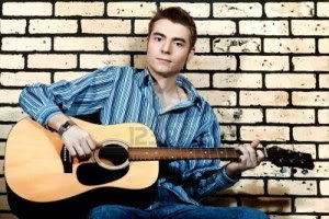 8550592-handsome-young-man-musician-playing-his-guitar-over-brick-wall-background