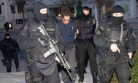 Greek police escort one of the suspected bank robbers after their arrest