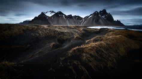 landscape sea coast black sand dry grass island  rocky