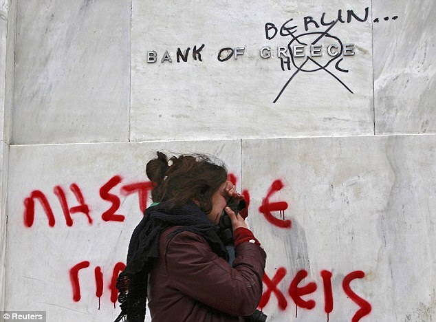 Αποπνικτική οικονομία: Μια γυναίκα πνίγει σε δακρυγόνα, όπως αυτή περνά μια παραμορφωμένη Τράπεζα της Ελλάδα σημάδι που κάνει αναφορά στο λιτότητας αιτήματα που οδηγείται από τη Γερμανία, μέσω