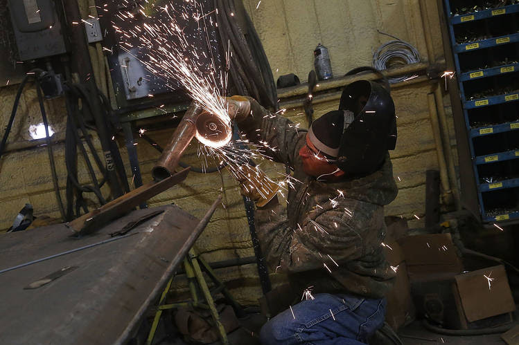 A welder for an oilfield service company works on a pipe for the fracking industry in the Permian Basin in Andrews, Texas, in January.