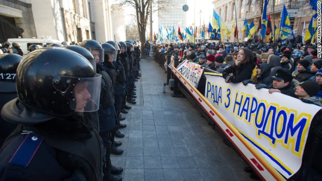 Police stand guard opposite a sea of protesters near the Ukrainian parliament in Kiev on Tuesday, December 3. Riot police lined up to protect the office of President Viktor Yanukovich, whose decision not to sign a landmark trade deal with the European Union sparked the public outrage.