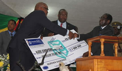 President Mugabe receives a US$1 million check from Murowa Diamonds managing director Mr Zebra Kasete while Youth Development, Indigenisation and Empowerment Minister Saviour Kasukuwere looks on in Masvingo on February 15, 2013. by Pan-African News Wire File Photos