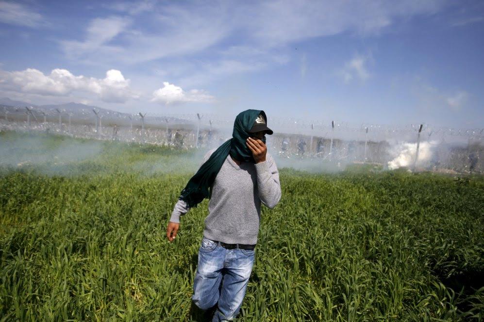 Un migrante se cubre la cara para evitar inhalar el gas.