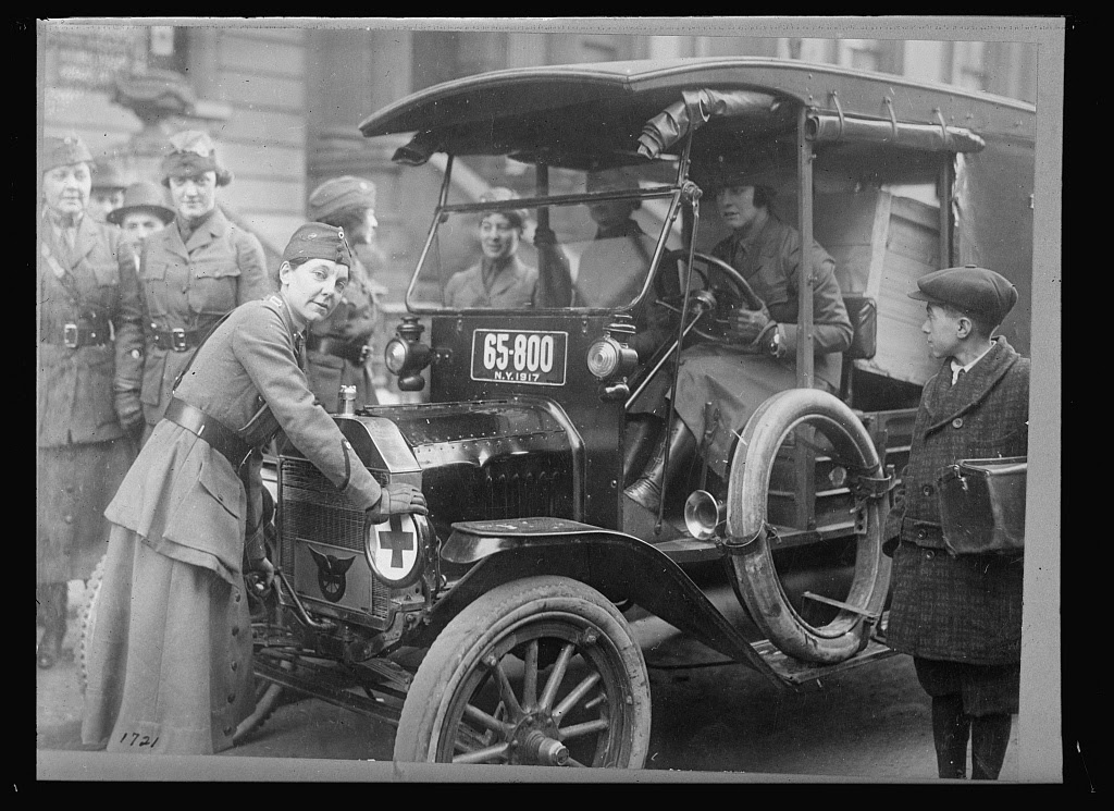 Womens part in the great war. Women are shown preparing to deliver various government packages. They are members of the National League for Women' Service, which is proving of great assistance to Uncle Sam in carrying on the Great War. Women are employed as drivers, ambulance drivers, messengers, etc. Captain A.B. Bayle is shown cranking the car, prior to making her rounds in New York. Photo from American National Red Cross Collection, between 1917 and 1920. //hdl.loc.gov/loc.pnp/anrc.06283