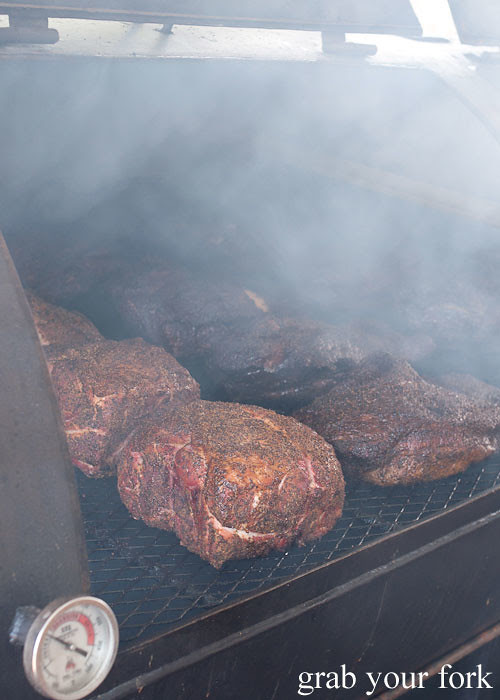 pork shoulders in the smoker at la barbecue austin texas