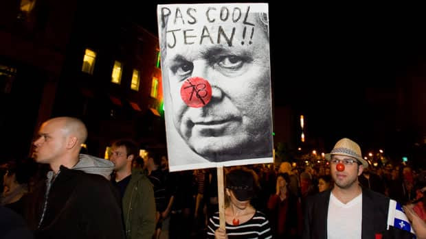 A protester holds a sign depicting Premier Jean Charest during a large rally designed as an act of defiance against Quebec's new law restricting protests.
