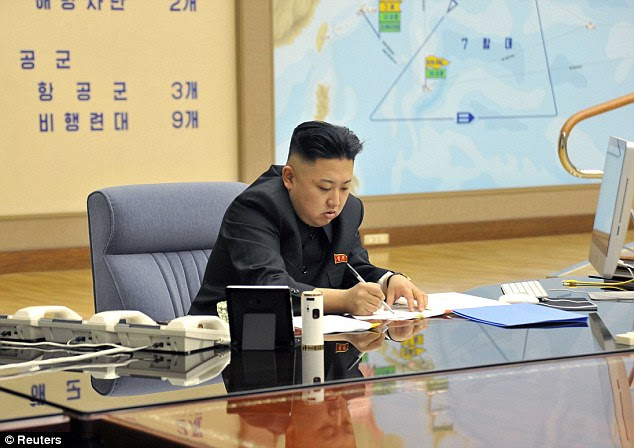 On a war footing: Kim Jong Un makes notes after ordering strategic rocket forces to be on standby to strike U.S. and South Korean targets at any time