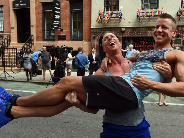 Justin Kattler e Tim Loecker, de Dallas, no Texas, celebram em frente ao bar Stonewall, conhecido pelo público gay e simpatizante, no bairro de West Village em Nova York, após o anúncio da liberação do casamento gay em todo o país (Foto: Timothy A. Clary/AFP)