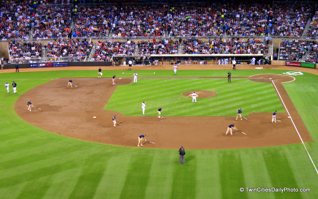The ground crew at Target Field smooths out the infield dirt between innings at the Minnesota Twins game.