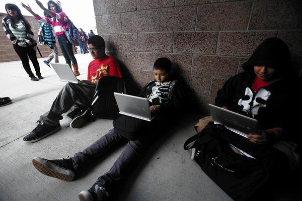 Perris middle school students Jacob Quinino, 13, left, Brian Guereque, 12, and Joshua Ortega, 12, use their Chromebook devices during lunch break.