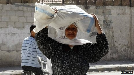 Woman carries sack of food aid on her head in Ghouta, Damascus. 6 Oct 2013