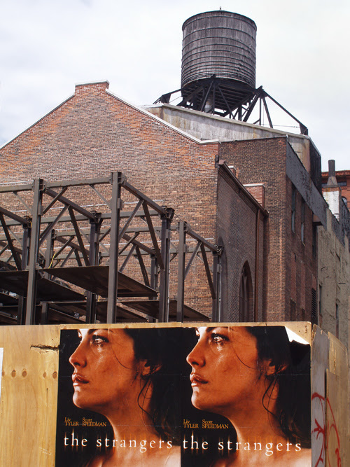 movie posters on temporary wall with water tower background, Manhattan, NYC