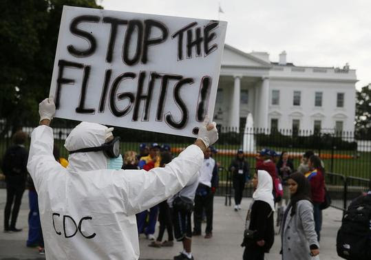 Protestor Jeff Hulbert of Annapolis, Maryland holds a sign as he demonstrates in favor of a travel ban to stop the spread of the Ebola virus, in front of the White House in Washington October 16, 2014.  REUTERS-Jim Bourg