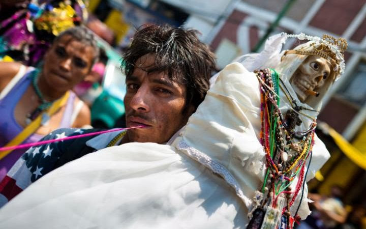 Follower of Santa Muerte holds a sacred statue during a ceremony in Tepito