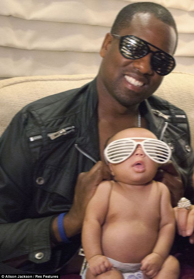 Proud: Kanye grins as he slips a pair of his famous shutter shades on his daughter