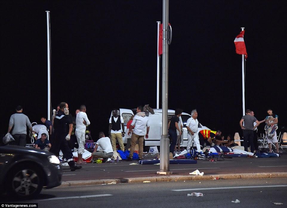 Os serviços de emergência trabalham para salvar os mortos e feridos em pavimentos ao longo do trecho milhas ao longo da estrada em Nice