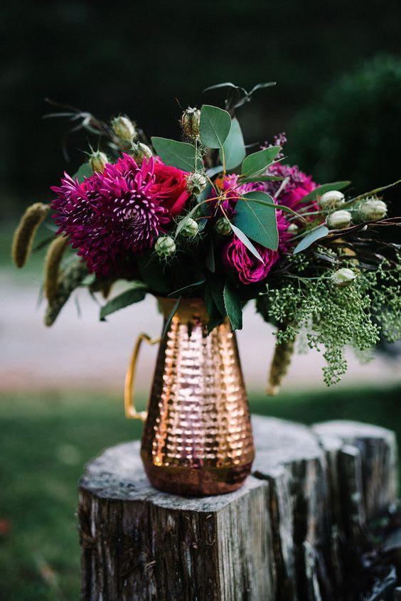 eine Kupfer-Krug mit Fett Pflaume-farbigen Blüten und saftigen grenenery für einen Tafelaufsatz