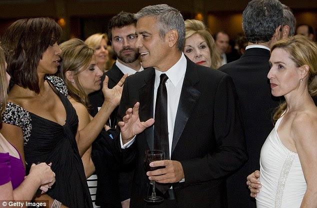 Senhoras homem: George Clooney garras um copo de vinho tinto como ele está cercado por hordas de admirar as mulheres