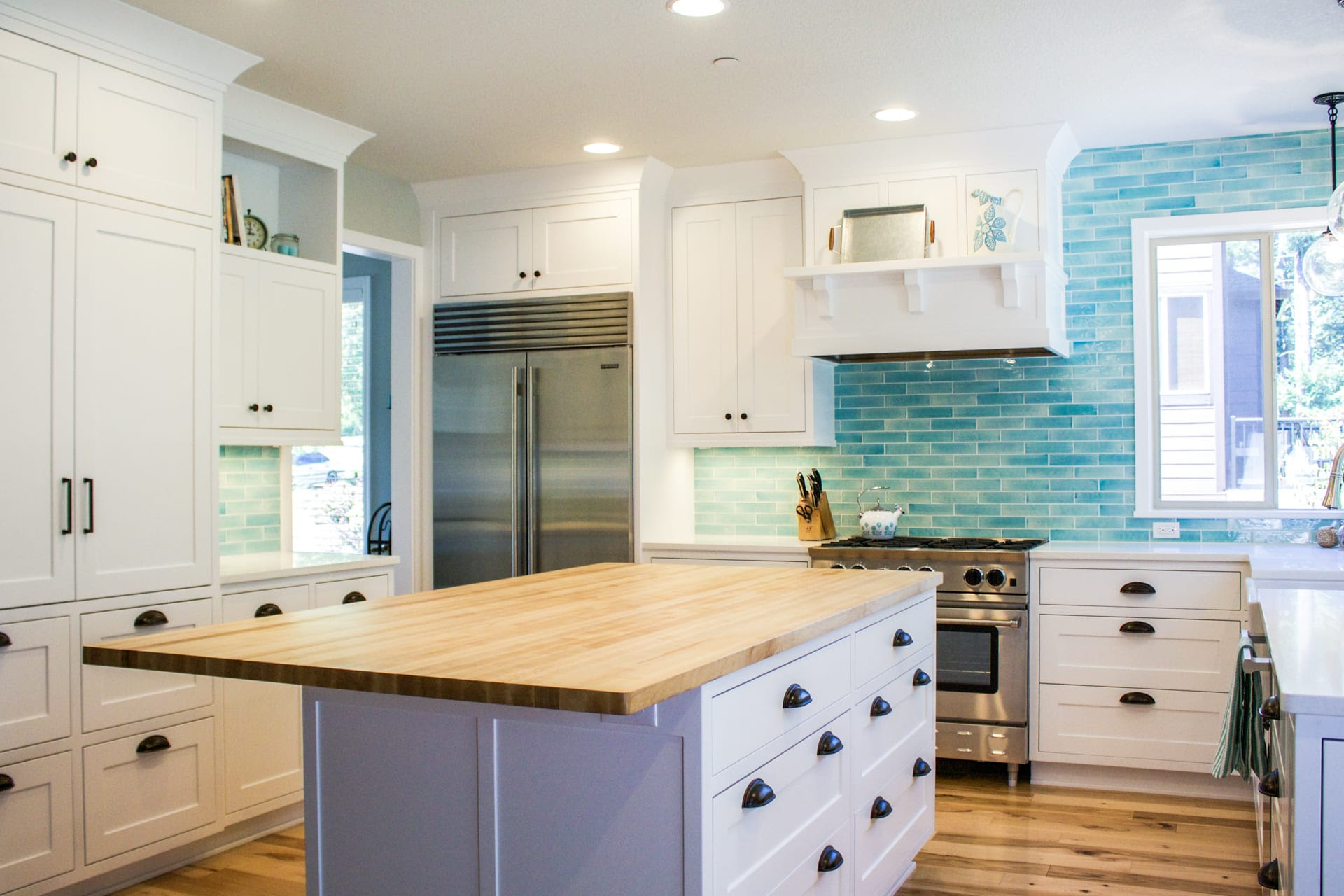 Custom designed kitchen with white cabinets and bold blue ...