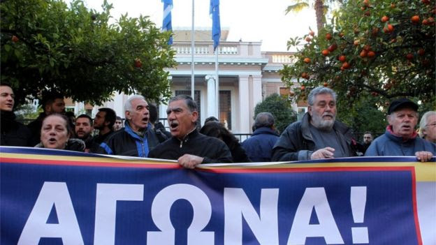 Protestors of the Communist-affiliated trade union PAME shout slogans during a protest against the new pension system reforms, outside the Maximos Mansion, in Athens, 8 January 2016