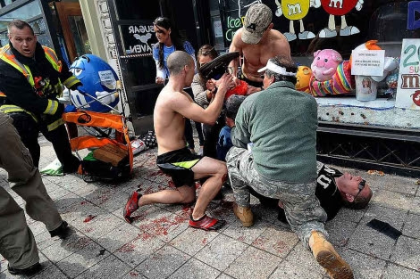 Varios testigos atienden a un herido por la explosión